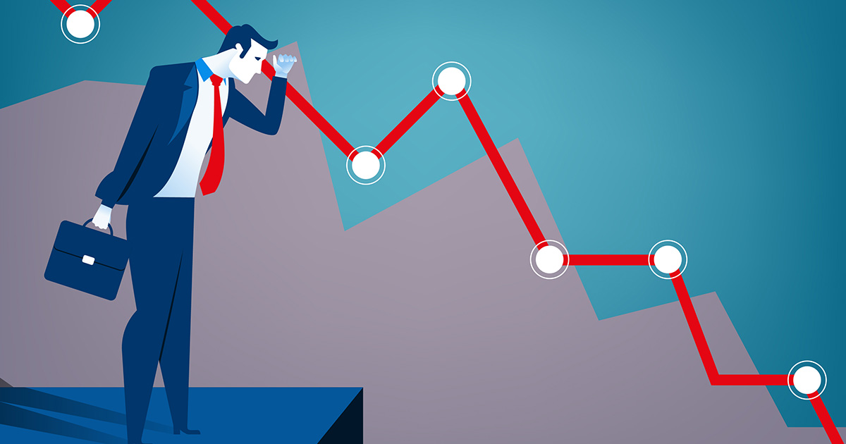 An illustration of a business man in a blue suit with a red tie holding a briefcase stands on a dark blue platform and looks downwards, along the sinking profile of a red line graph, which remains visible in the background of the frame and is punctuated by a series of white dots