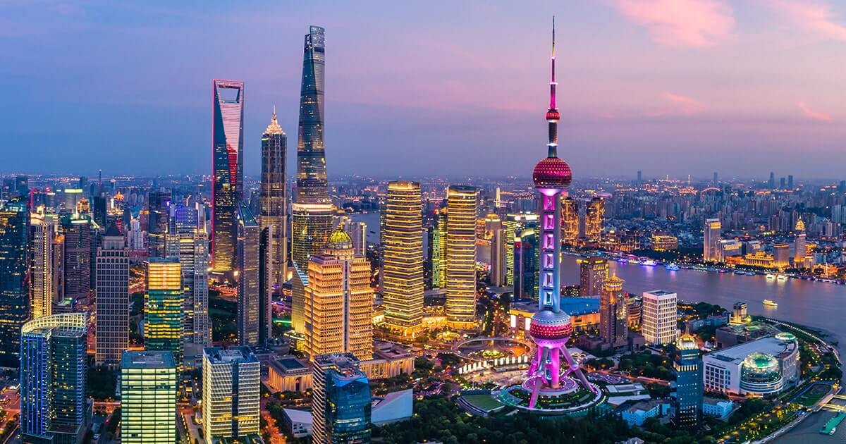 A panorama of the Shanghai skyline can be seen in the twilights hours, the sun having descended upon the horizon as a partially cloudy pink-tinged blue and grey sky succumbs to the onset of dusk, while the city below appears brightly illuminated in varying shades of gold, yellow and red, with many of its iconic buildings standing proudly upright, notably the Oriental Pearl Tower which features prominently to the right of the foreground, glistening in hot pink and purple tones, whilst a cluster of other skyscrapers, including the Shanghai World Financial Center and Shanghai Tower, extend upwards to the left of the frame.
