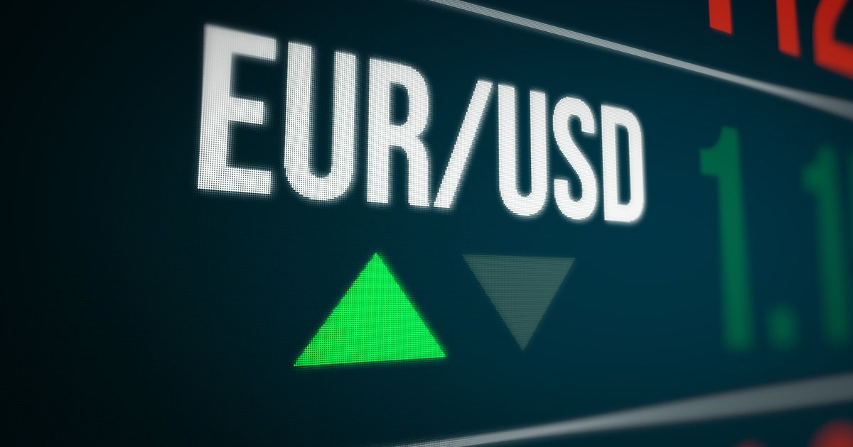 The characters EUR/USD appear, positioned at an oblique angle, against a black computer screen background, hovering above two arrowhead symbols, with a green one pointing upwards, and a greyed out one pointing downwards