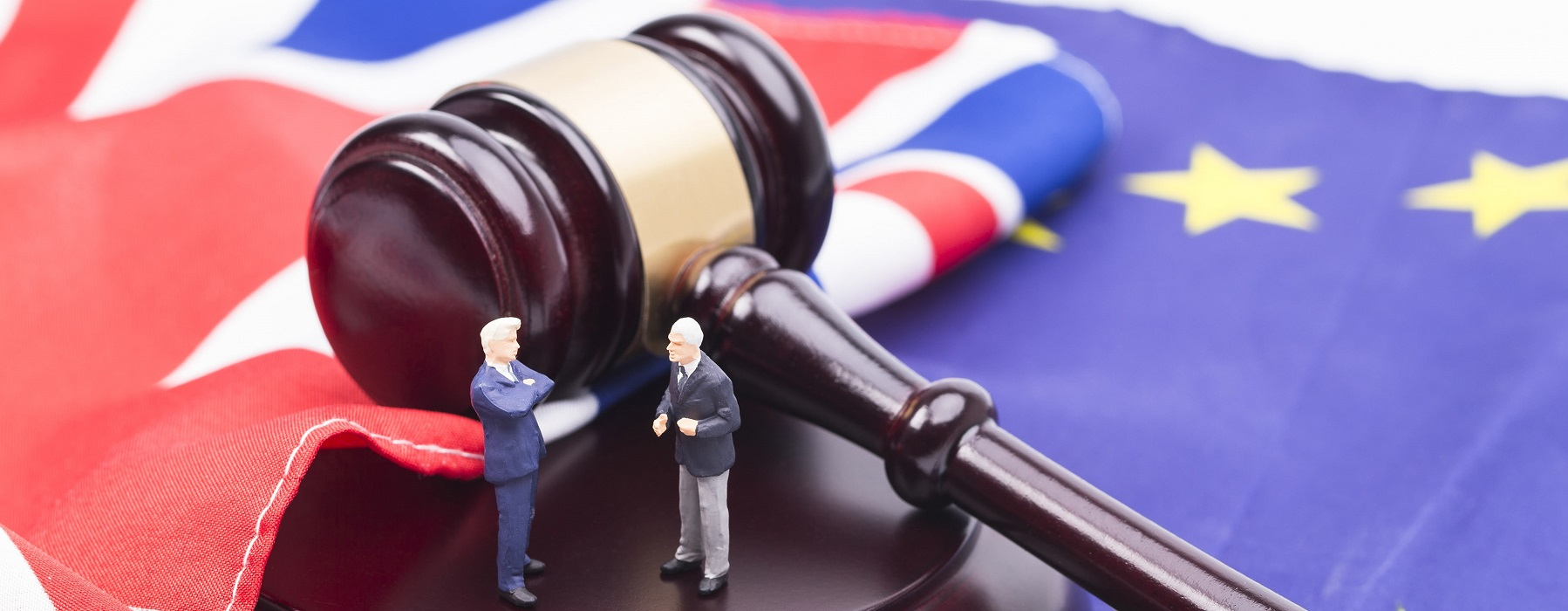Two small male figurines engage in discussion next to a gavel resting on the flags of the EU and the United Kingdom