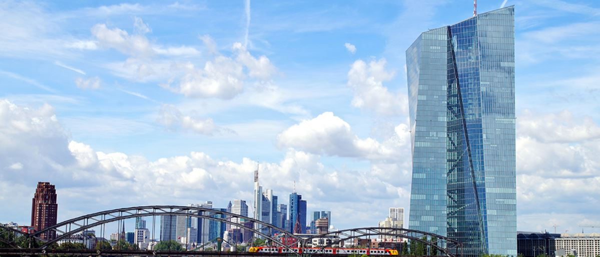 Under a blue and sun-drenched sky, with minimal cumulus cloud cover, the skyscraper building of the European Central Bank is seen standing tall in the foreground, with the Main river remaining visible as it flows into the background, passing under a steel truss bridge, as Frankfurt's skyline appears clustered on the horizon