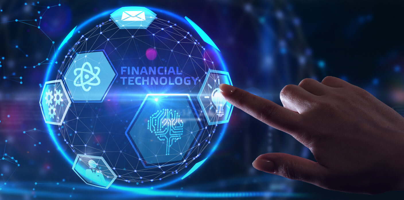 """Female hand points at a symbol of a light-bulb on a blue luminous globe. The globe features the text """"financial technology"""""""