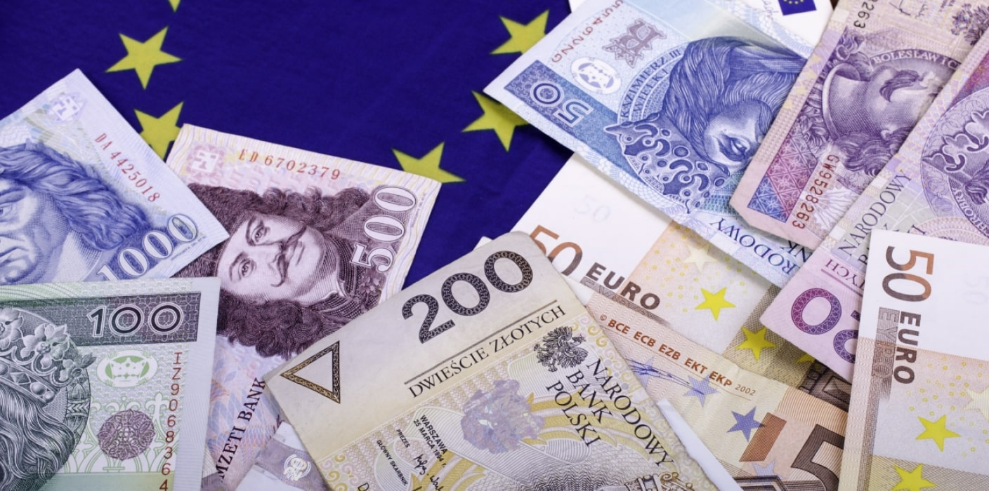 A view of bank notes of different currencies including the euro and the zloty and a partial view of the European flag which has a blue background and yellow stars