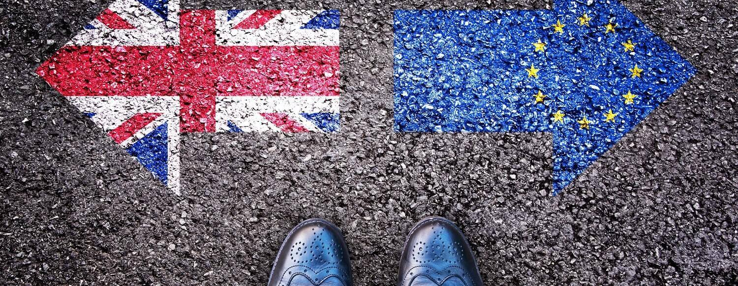 Aerial view of a pair of men's brogues againt a tarmac background with the British and European Union flags visible on either side