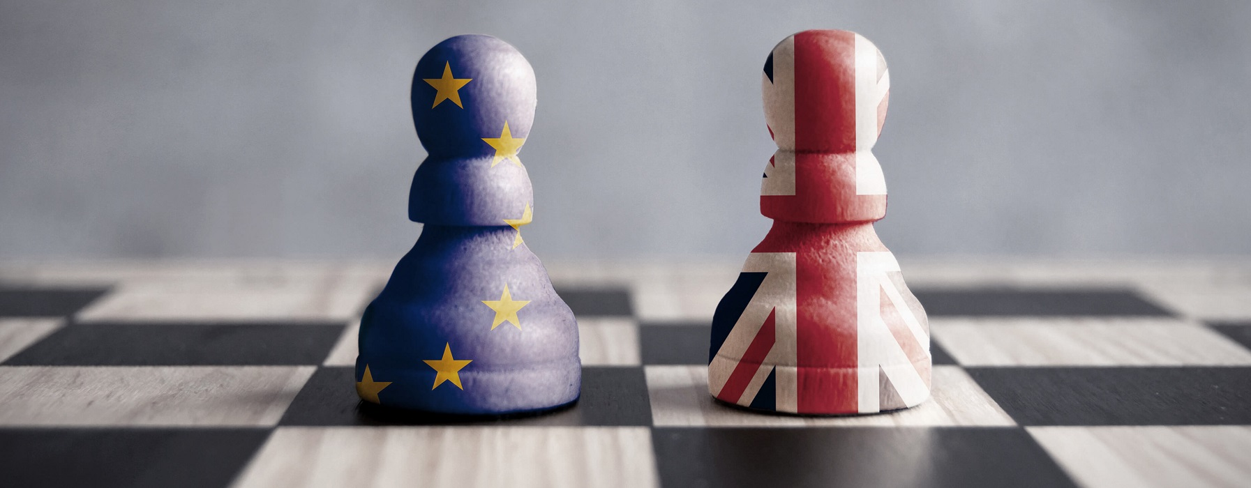 Two pawns stand alongside one another on a chessboard, one draped in the EU flag, the other in that of the United Kingdom