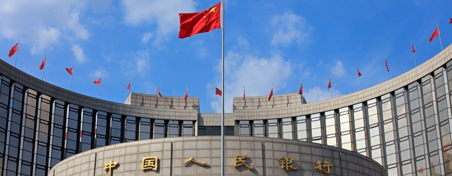 Viewed head on, the concentric cylindrical concrete roof and upper floors of the People's Bank of China building can be seen, centrepieced by a large, billowing Chinese flag, while smaller Chinese flags stand atop the structure in the background.