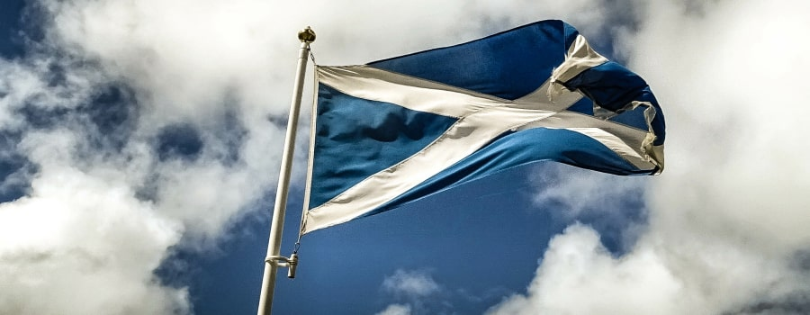 Seen from below, a Scottish flag is seen billowing in the wind atop a flagpole, against a partially cloudy blue sky, exhibiting similar blue and white tones to the flag itself.