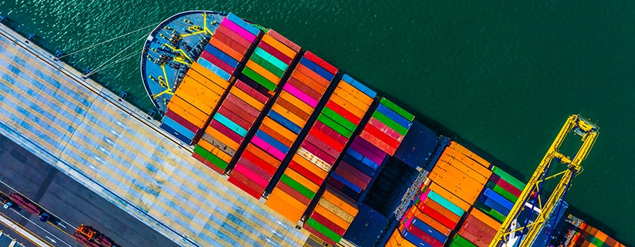 Viewed directly from above, at an oblong angle, a large container ship can be seen, replete with a multitude of tightly packed, multi-coloured rectangular shipping containers, while the vessel itself remains docked next to a concrete-paved loading bay,  which flaunts a series of parallel grey and yellow strips along its surface.