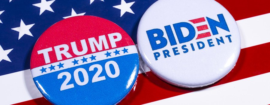 "Against a diagonally positioned backdrop of the US flag, two electoral badges sit side by side, in an oblong fashion, with the one on the left displaying the red and white electoral logo of candidate Donald Trump, with the text ""Trump 2020"" scrawled upon it, while the one on the right, in white with blue and red lettering, represents candidate Joe Biden and reads ""Biden President""."